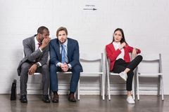 Asian businesswoman looking at multicultural businessmen gossiping while waiting. For job interview royalty free stock image