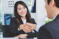 Asian businesswoman making handshake with a businessman Stock Photo