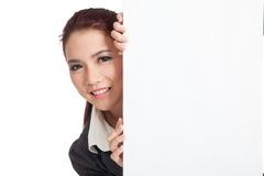 Asian businesswoman peeking from behind a blank si Stock Photos
