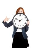Asian businesswoman point to a clock over her face Stock Image