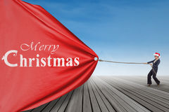 Asian businesswoman pulling christmas banner Royalty Free Stock Photo