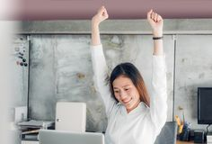 Asian businesswoman raise arm up stretching in front of desk fro. M work on notebook screen in office,Office lifestyle concept stock image