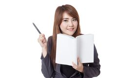 Asian businesswoman read a book and point a pen to her right Stock Photography