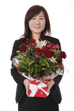 Asian Businesswoman With Red Roses. Beautiful Young Asian (Chinese) Businesswoman With Red Roses In Gift Box stock photo