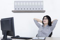 Asian businesswoman relaxing in the office. Picture of Asian businesswoman relaxing on the office chair while sitting with a computer on the desk Stock Image