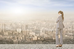 Asian businesswoman on roof looking at city Royalty Free Stock Images
