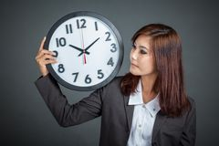 Asian businesswoman show a clock on her shoulder Stock Photos