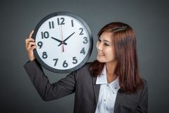 Asian businesswoman show a clock on her shoulder and smile Stock Images