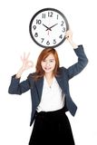 Asian businesswoman show OK sign with clock over head Royalty Free Stock Photo