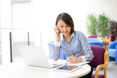 Asian Businesswoman sitting at her desk in an office Stock Photography