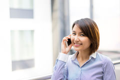 Asian Businesswoman sitting at her desk in an office Stock Photo