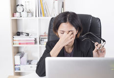 Asian businesswoman sitting at the table computer in office. With massaging his nose and keeping eyes royalty free stock photography