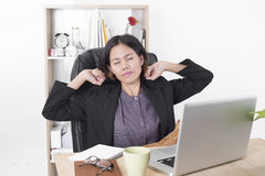 Asian businesswoman sitting at the table computer in office. With stretching arms Royalty Free Stock Images