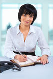Asian businesswoman sitting at table in office writing in notepa Royalty Free Stock Photos