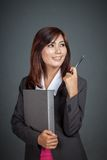 Asian businesswoman smile point with a pen look at her left Royalty Free Stock Images