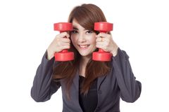 Asian businesswoman smile put her face between drumbbells Royalty Free Stock Photo