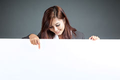 Asian businesswoman stand behind a blank banner , point down and. Smile on gray background Stock Image