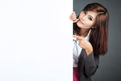 Asian businesswoman stand behind a blank banner and point Royalty Free Stock Image
