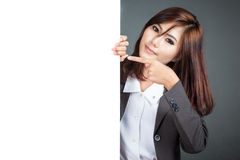 Asian businesswoman stand behind a blank banner and point Royalty Free Stock Photo