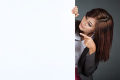 Asian businesswoman stand behind a blank banner , point  and loo Stock Images