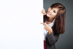 Asian businesswoman stand behind a blank banner , point and smil Royalty Free Stock Images