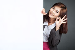 Asian businesswoman stand behind a blank banner show Ok sign Royalty Free Stock Image