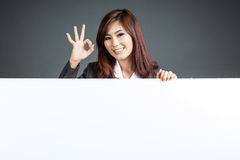 Asian businesswoman stand behind a blank banner show Ok sign Stock Images