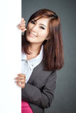 Asian businesswoman stand behind a blank banner and smile Royalty Free Stock Images
