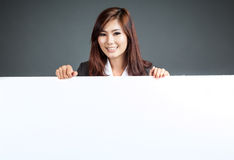 Asian businesswoman stand behind a blank banner and smile Royalty Free Stock Photo