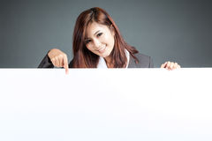 Asian businesswoman stand behind a blank billboard , point down. And smile on gray background Stock Photos