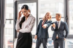Asian businesswoman standing in office, businessmen behind gesturing and laughing Royalty Free Stock Image