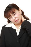 Asian businesswoman suffers from neck ache. Studio shot of young Asian woman on white background stock photography
