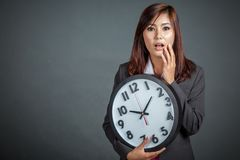 Asian businesswoman surprised hold a clock Royalty Free Stock Photography
