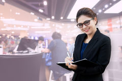 Asian businesswoman take notes with counter service. Take photo with DSLR camera and process blending in photoshop program Stock Photography