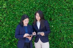 asian businesswoman team taking about work outside office at green leaves hedge,leave space for adding text,Female leadership con royalty free stock images