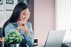Asian businesswoman thinking with pencil and looking down to lap. Top computer screen for planning work with smile face in office,Office lifestyle concept stock images