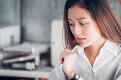 Asian businesswoman thinking with pencil and looking down to lap. Top computer screen for planning work in office,Office lifestyle concept Royalty Free Stock Photography