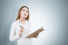 Asian businesswoman thinking about success. Thoughtful asian female with clipboard and pen in hands on light grey background with copy space. She is thinking Royalty Free Stock Photo