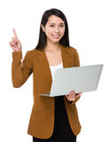 Asian businesswoman use of notebook computer and finger point up Royalty Free Stock Image