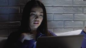 Asian businesswoman using laptop at night, drinking water, freelance overwork stock video