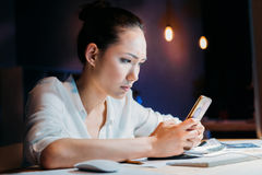 Asian businesswoman using smartphone, working late at the office Stock Photography
