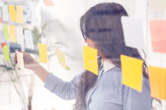 Asian businesswoman using sticky notes on wall Royalty Free Stock Image