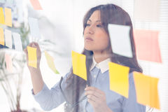 Asian businesswoman using sticky notes on wall Stock Photo