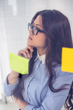 Asian businesswoman using sticky notes on wall Stock Photography