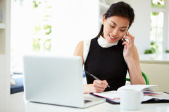 Asian Businesswoman Working From Home Using Mobile Phone Stock Images