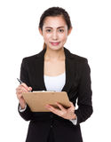 Asian businesswoman write on clipboard Stock Photos