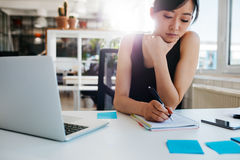 Asian businesswoman writing notes on notepad Stock Image