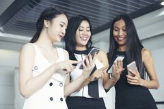 Asian Businesswomen with partner discuss about the detail of work on smartphone and business women smiling stock image