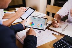 Asian businesswomen using tablet for analysis documents and graph financial diagram working in meeting royalty free stock photo