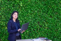 Asian Busineswoman using laptop computer working outside office. At green hedge,Moblie office concept Stock Images
